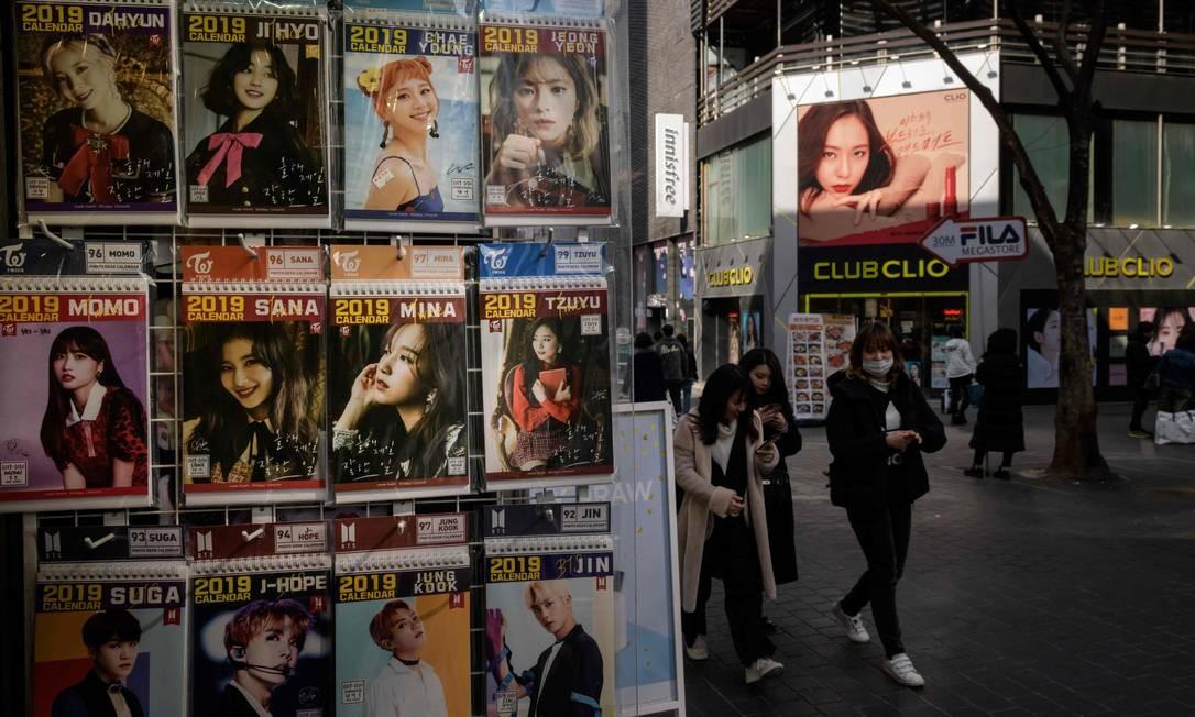 Propaganda K-pop é exibida fora de uma loja no distrito comercial de Myeongdong, em Seul. As estrelas do K-pop e os atores, temendo a estigmatização, se apressaram em negar que aparecem em vídeos secretos de cantores homens, ilustrando as preocupações das mulheres sobre a culpabilização das vítimas diante dos duradouros valores sociais conservadores da Coreia do Sul Foto: ED JONES / AFP