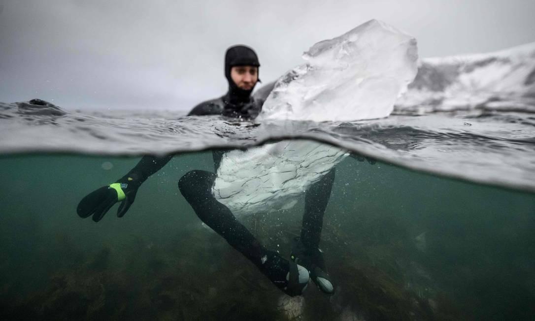 O surfista sueco Pontus Hallin espera por ondas sentado em sua prancha de gelo no local de surf Delp, próximo a Straumnes, nas Ilhas Lofoten, sobre o Círculo Polar Ártico Foto: OLIVIER MORIN / AFP