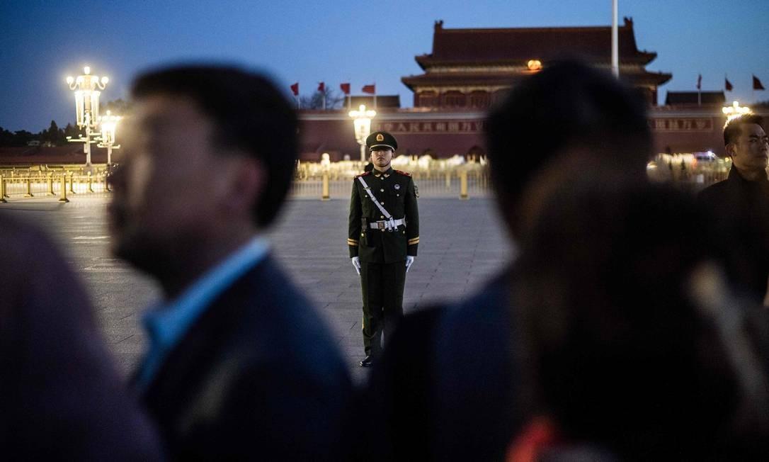 Um policial paramilitar em posição de guarda enquanto os turistas esperam pela cerimônia diária de levantar bandeiras na Praça da Paz Celestial antes da sessão de encerramento do Congresso Nacional do Povo (NPC), no Grande Salão do Povo, em Pequim Foto: FRED DUFOUR / AFP