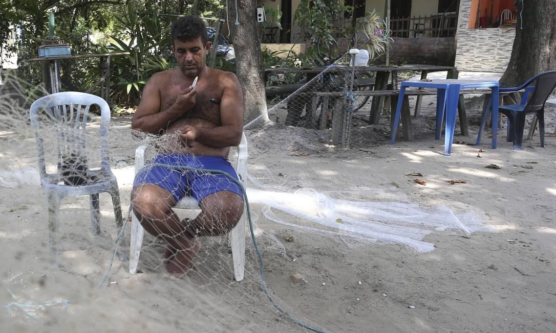 Pescador trança rede no terreno que foi desaproriado pela Justiça, em frente às casas dos caiçaras Foto: Pedro Teixeira / Agência O Globo
