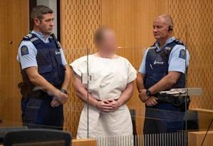 Brenton Tarrant, autor do atentado contra duas mesquitas de Christchurch, Nova Zelândia, é escoltado por dois policiais na sua apresentação em um tribunal local, com o rosto distorcido por determinação da Justiça Foto: MARK MITCHELL/AFP