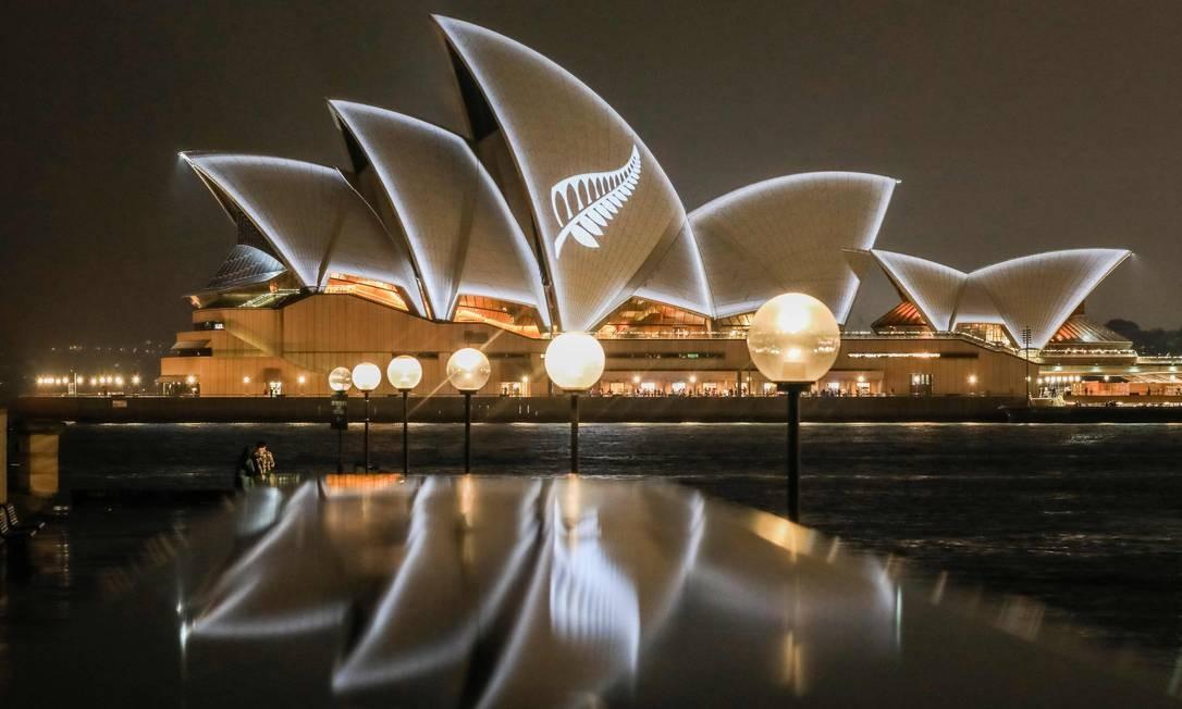 As velas da Ópera de Sydney, na autrália, vistas iluminadas com o desenho da samambaia de prata da Nova Zelândia, em uma demonstração de solidariedade às vítimas dos ataques da mesquita de Christchurch, ocorridos na última sexta-feira (15) Foto: SALTY DINGO / AFP
