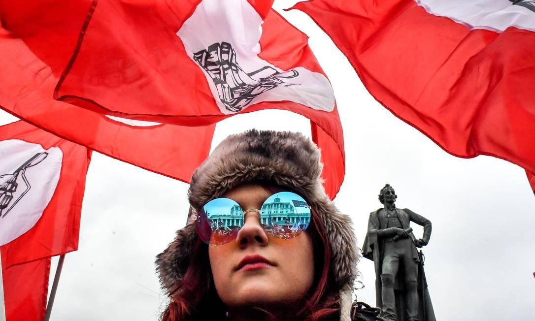 """Um membro do movimento russo-bolchevique nacional assiste a uma manifestação da oposição """"Pela Rússia! Justiça! New Deal"""", no centro de Moscou. Os participantes exigem mudanças no curso socioeconômico do desenvolvimento do país Foto: YURI KADOBNOV / AFP"""