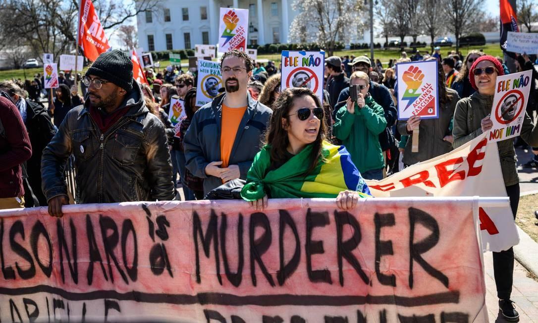 """""""Not him"""". Brasileiros e e americanos protestam em frente à Casa Branca, em Washington, contra a visita do presidente Jair Bolsonaro aos Estados Unidos Foto: ERIC BARADAT / AFP"""
