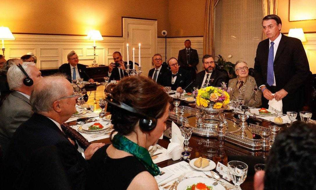 Escritor Olavo de Carvalho, à direita do presidente brasileiro, Jair Bolsonaro (de pé), durante jantar em Washington Foto: Divulgação