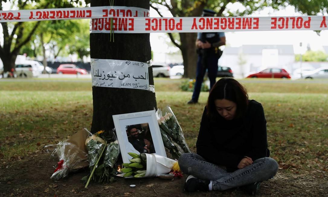 Uma mulher senta ao lado de flores e mensagens em um memorial para as vítimas do massacre das mesquitas na Nova Zelândia Foto: JORGE SILVA / REUTERS