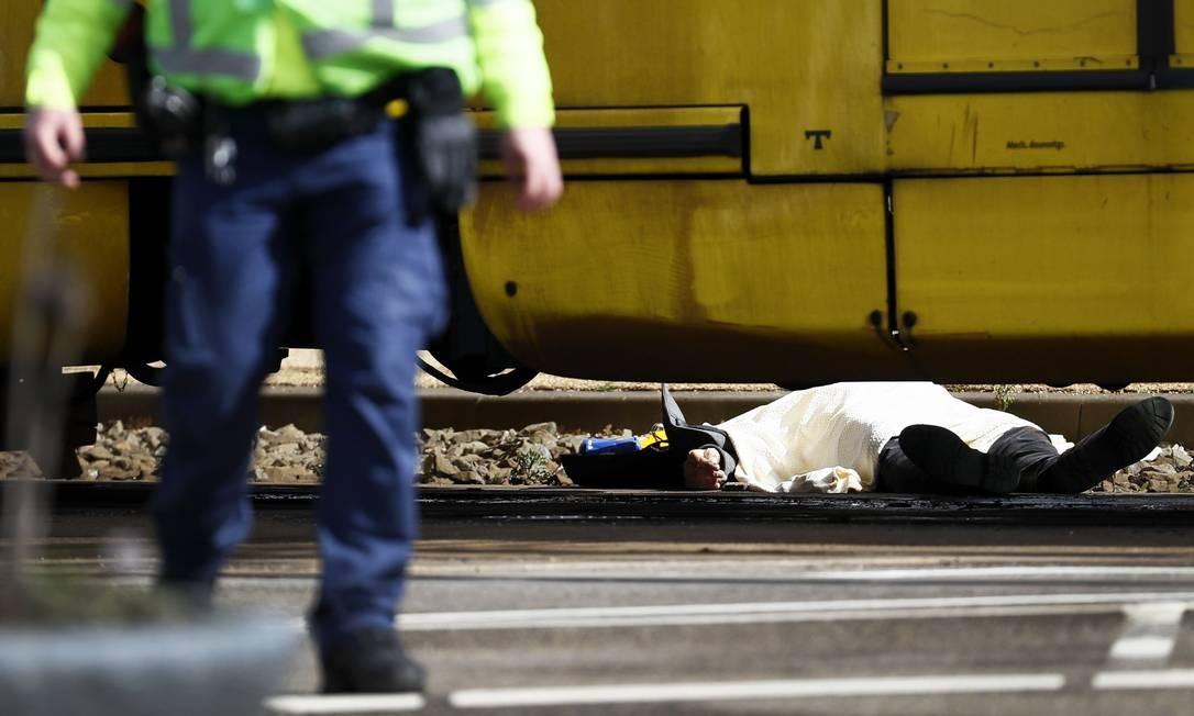 Uma pessoa morreu nesta segunda-feira 18 na cidade holandesa de Utrecht. Na foto, um policial caminha perto da vítima do atirador que abriu fogo em uma estação de bonde Foto: ROBIN VAN LONKHUIJSEN / AFP