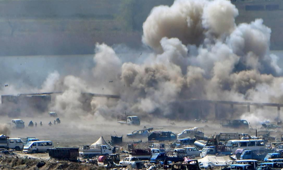 Pessoas são vistas fugindo de um bombardeio enquanto destroços voam sobre a última posição remanescente do grupo Estado Islâmico Foto: GIUSEPPE CACACE / AFP