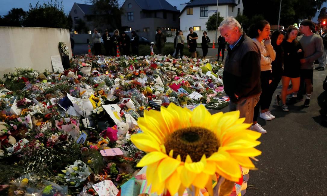 Pessoas visitam memorial pelas vítimas do atentado montado em frente à mesquita de Al Noor, em Christchurch, Nova Zelândia: dono da loja que vendeu armas usadas no ataque não viu nada fora do comum no terrorista Foto: JORGE SILVA/REUTERS