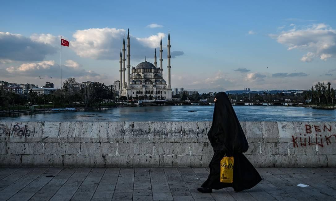 Uma mulher vestindo um nicabe caminha sobre a ponte histórica de Taskopru, perto da mesquita de Sabanci, em Adana, no sul da Turquia Foto: OZAN KOSE / AFP