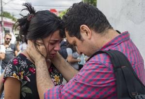 Alunos e pais se reencontram na Escola Estadual Raul Brasil, em Suzano. Pai de Samuel, uma das vítimas do ataque, Gercialdo Melquiades, consola a estudante Isabella de Oliveira, a primeira aluna a ficar na mira do atirador Foto: Edilson Dantas / Agência O Globo