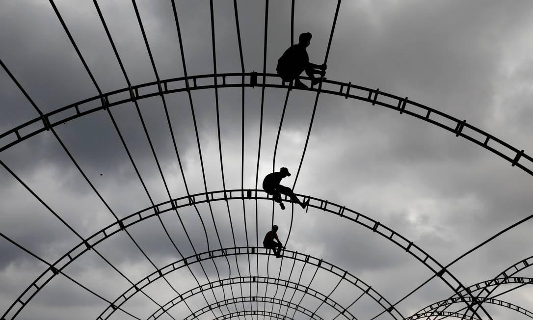 Homens trabalham em cima de uma marquise para um evento em Colombo, Sri Lanka Foto: DINUKA LIYANAWATTE / REUTERS