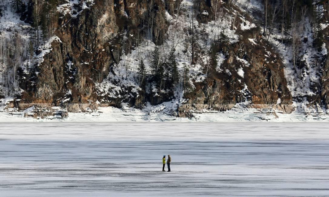 Um casal conversa sobre o gelo do rio Yenisei, congelado dsurante a primavera em Krasnoyarsk, Rússia Foto: ILYA NAYMUSHIN / REUTERS