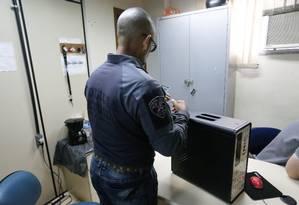 EXT CI Rio de Janeiro -policial examina comoutador usado por adolescente - Foto Guilheme Pinto / Agência O Globo Foto: Guilherme Pinto / Agência O Globo