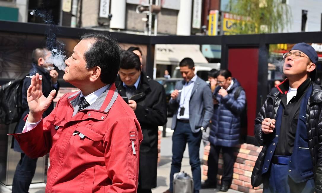 Fumantes utilizam área designada para eles no distrito de Shimbashi, em Tóquio Foto: CHARLY TRIBALLEAU / AFP