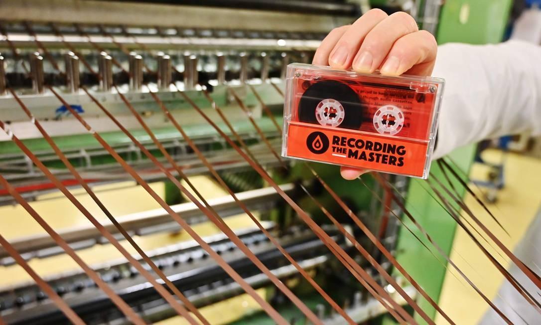 Um homem segura uma fita cassete feita com tarjas magnéticas na planta de produção de Mulann, em Avranches, Noroeste da França. Mulann atua na retirada de tarjas magnéticas de cartões, como os bancários, e para uso de áudio, como fita cassete vintage Foto: CHARLY TRIBALLEAU / AFP