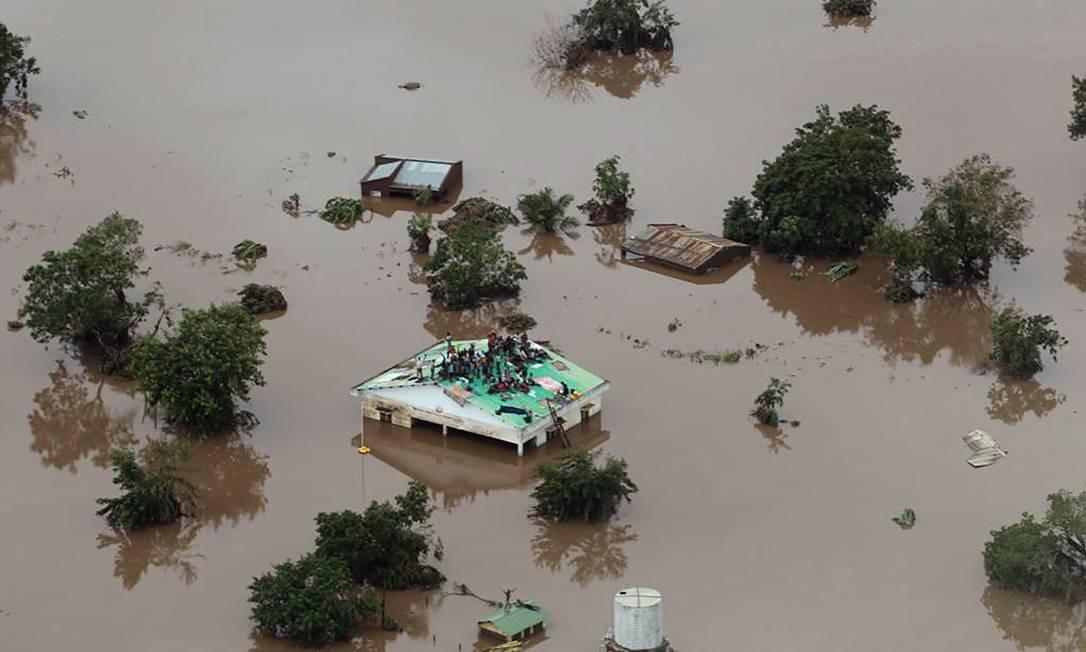 Imagem do dia 18 de março divulgada nesta terça-feira (19) pela Mission Aviation Fellowship mostra pessoas sobre o telhado de uma casa em meio à inundação em uma área afetada pelo ciclone Idai, na cidade da Beira, em Moçambique. O ciclone que atingiu Moçambique e Zimbábue já matou cerca de 180 pessoas e várias outras estão desaparecidas Foto: RICK EMENAKET / AFP