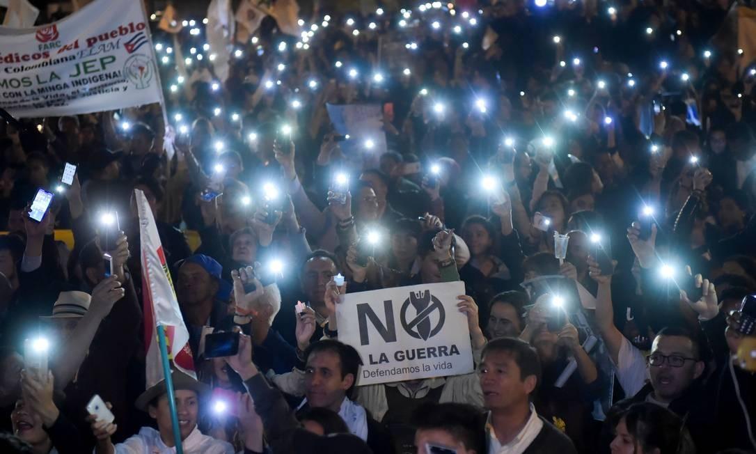 """Manifestantes vão às ruas contra uma reforma proposta pelo governo para a Jurisdição Especial pela Paz (PEC) com uma placa que diz """"Não à guerra"""", em Bogotá, Colômbia Foto: RAUL ARBOLEDA / AFP"""