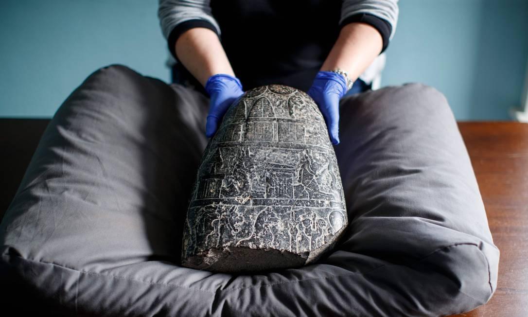 No Museu Britânico, em Londres, um assistente de galeria posa com um kudurru cuneiforme babilônico (pedra limite) que havia sido saqueado do Iraque. O kudurru, que foi apreendido no aeroporto de Heathrow, em Londres, em 2012, foi entregue aos representantes da embaixada do Iraque hoje no Museu Britânico Foto: TOLGA AKMEN / AFP