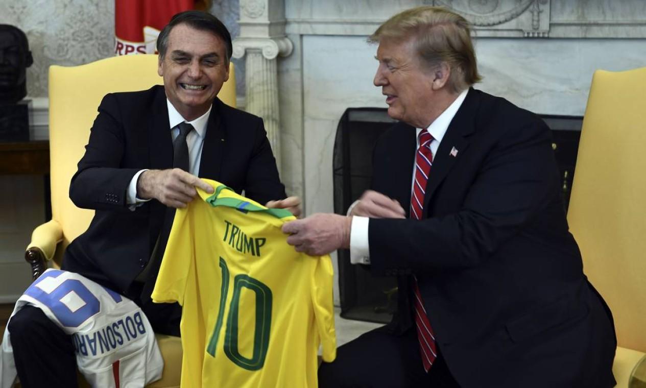 Trump e Bolsonaro trocam camisas de equipes de futebol no Salão Oval da Casa Branca; americano ganhou a camisa 10 de Bolsonaro Foto: BRENDAN SMIALOWSKI / AFP