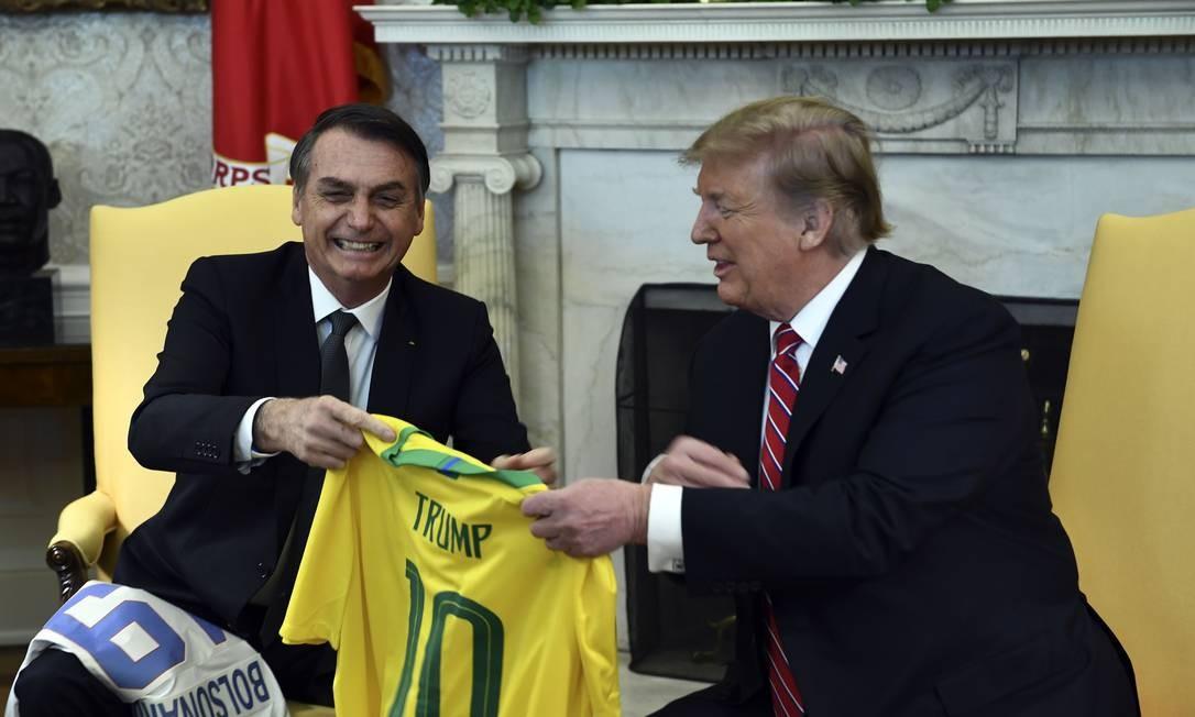 Presidente do Brasil, Jair Bolsonaro, e presidente dos EUA, Donald Trump, trocam presentes no Salão Oval da Casa Branca Foto: BRENDAN SMIALOWSKI / AFP