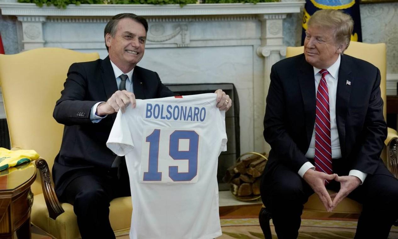 Bolsonaro exibe camisa da seleção dos EUA com seu nome, um presente de Trump Foto: KEVIN LAMARQUE / REUTERS