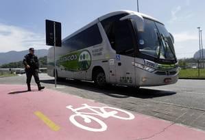 Policial passa ao lado do ônibus que atropelou o ciclista na Barra Foto: Marcio Alves / Agência O Globo