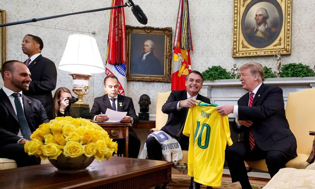 Jair Bolsonaro entrega uma camisa personalizada, simbolizando o esporte nacional, a Donald Trump Foto: Agência O Globo