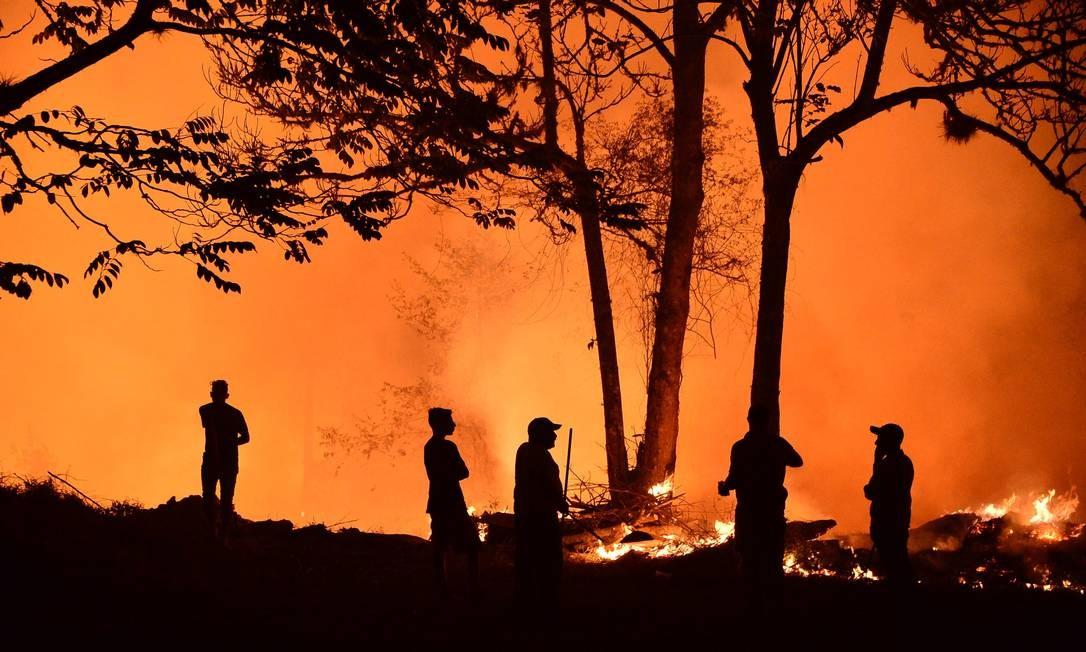 Moradores olham para um incêndio florestal no departamento de El Hatillo, Francisco Morazan, Honduras. Centenas de hectares foram destruídos pelas chamas em El Hatillo, perto do parque nacional La Tigra Foto: ORLANDO SIERRA / AFP