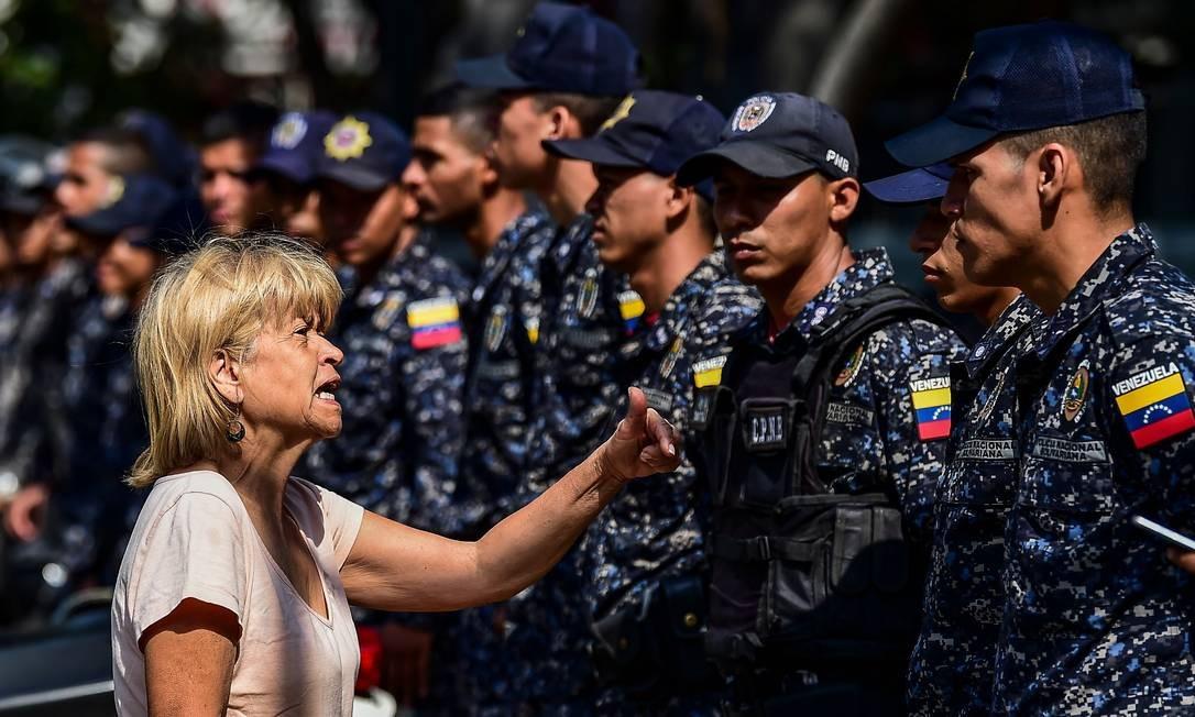 Mulher discute com um policial antes de uma manifestação convocada por líderes sindicais para exigir proteção trabalhista contra a demissão de funcionários públicos em Caracas. Foto: RONALDO SCHEMIDT / AFP