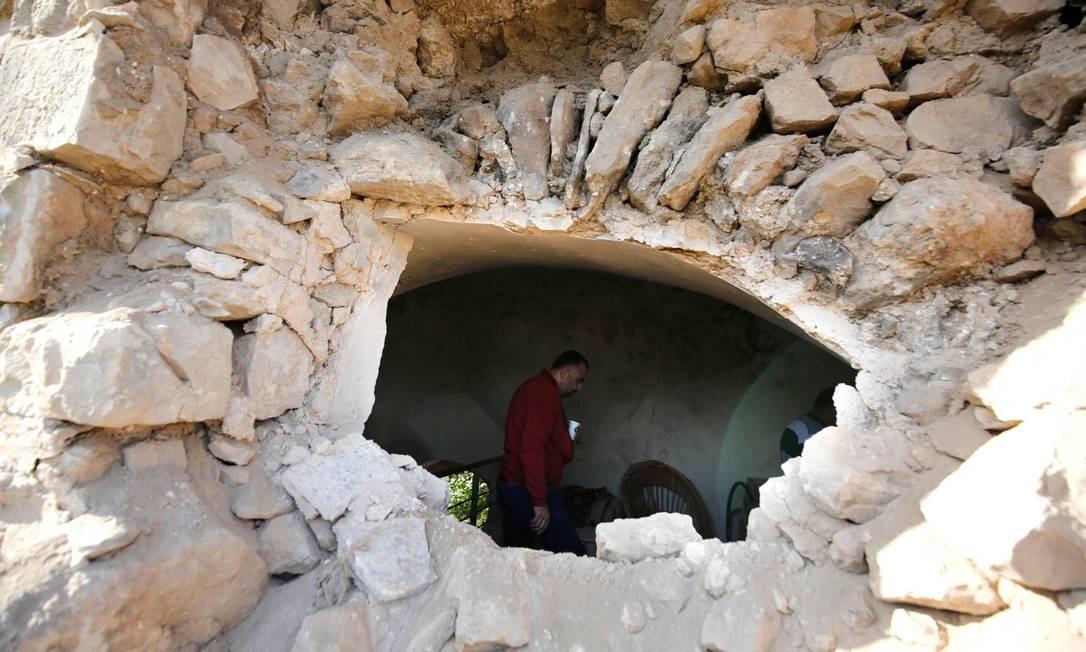 Palestino está dentro de um prédio que foi invadido por tropas israelenses na aldeia de Abwein, no norte de Ramallah. Foto: ABBAS MOMANI / AFP