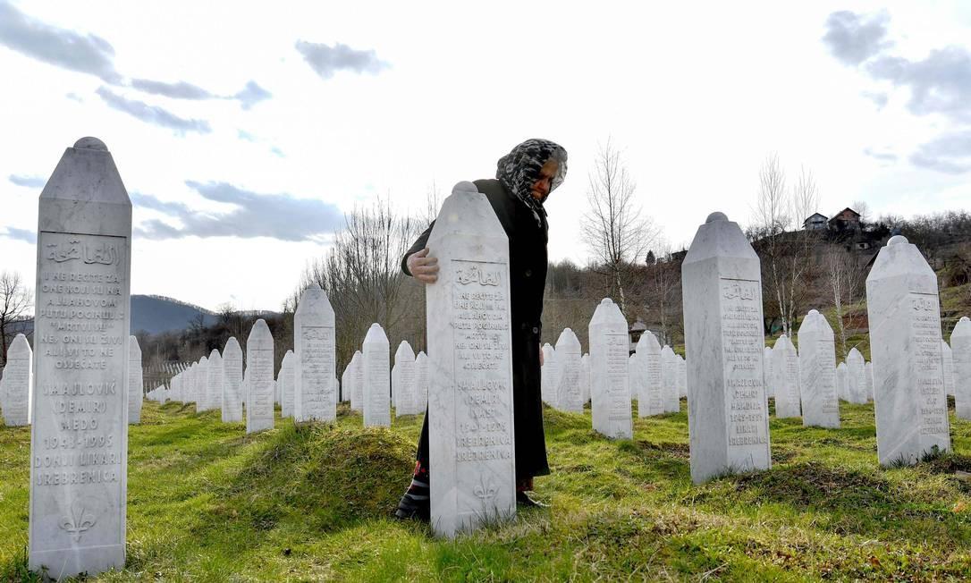 Sobrevivente do massacre de Srebrenica em julho de 1995, fica ao lado da lápide do marido, durante visita ao cemitério memorial de Srebrenica. O massacre de Srebrenica aconteceu em campanha de limpeza étnica e foram mortos mais de 8.000 homens e meninos muçulmanos. Foto: ELVIS BARUKCIC / AFP