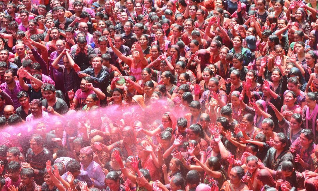 Indianos são pulverizados com água colorida celebrando o festival de Holi no Kalupur Swaminarayan Temple. Holi, o popular festival de primavera Hindu de cores é observado na Índia no final do inverno temporada na última lua cheia do mês lunar. Foto: SAM PANTHAKY / AFP