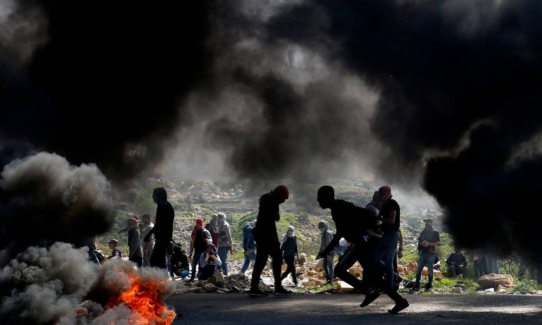 Manifestantes palestinos da Universidade Birzeit se protegem durante confrontos com forças israelenses em Ramallah, perto do assentamento judaico de Beit El, na Cisjordânia Foto: ABBAS MOMANI / AFP