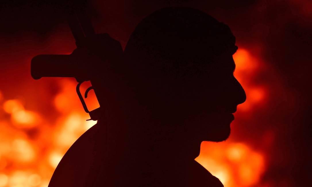 Um combatente das Forças Democráticas da Síria (SDF), liderado por curdos, está na frente de uma fogueira durante as celebrações de Nowruz (Noruz) perto da aldeia de Baghouz no interior da província síria oriental de Deir Ezzor Foto: GIUSEPPE CACACE / AFP