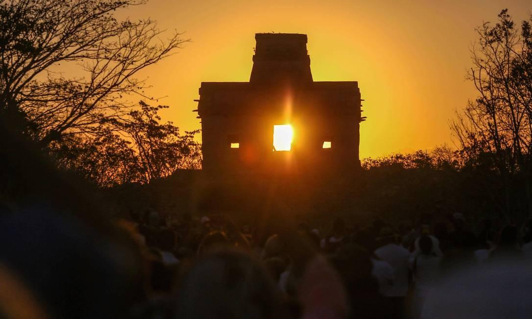 O sol brilha diretamente através da porta do Templo das Sete Bonecas, quando as pessoas se reúnem para celebrar o equinócio da primavera no sítio arqueológico maia de Dzibilchaltun, no estado de Yucatan, no México Foto: HUGO BORGES / AFP