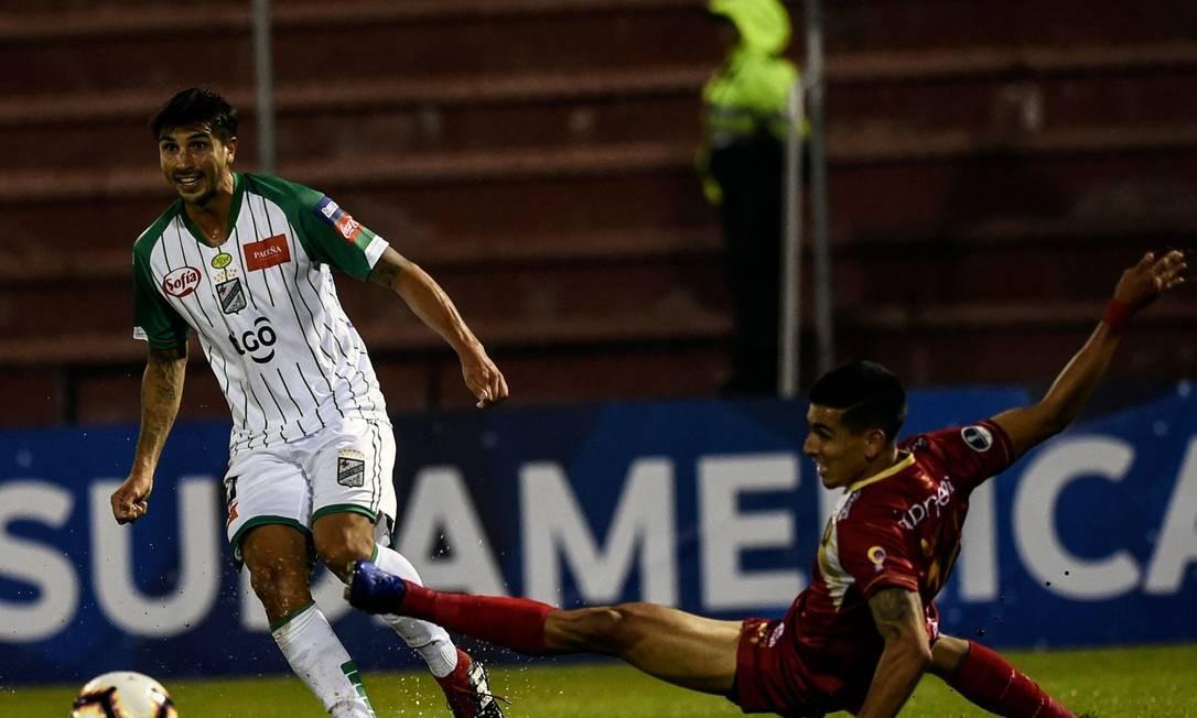 Lucas Mugni recebe a marcação de Daniel Munoz, do Rionegro Foto: JOAQUIN SARMIENTO / AFP