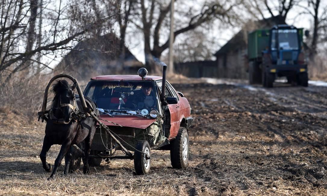"""O fazendeiro Alexei Usikov, de 31 anos, exibe sua invenção: uma carroça puxada a cavalo feita de um velho carro, modelo Audi 80, na vila de Knyazhitsy, a 230 quilômetros a leste de Minsk, capital da Bielorrússia. Desde criança, Alexei Usikov gosta de criar coisas. Sua mais recente invenção é o que ele chama de """"cavalo móvel"""" Foto: SERGEI GAPON / AFP"""