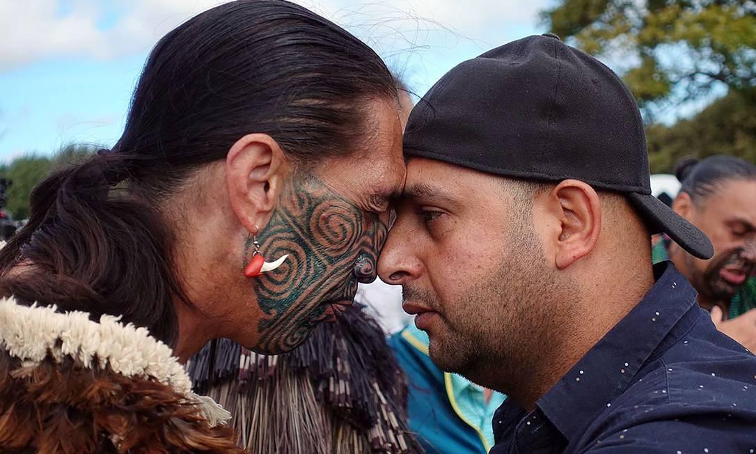 Um muçulmano e um nativo fazem a tradicional saudação maori hong', com um toque de nariz, durante uma reunião para orações congregacionais, seguida de dois minutos de silêncio, em homenagem às vítimas do massacre em Christchurch, na Nova Zelândia Foto: JEROME TAYLOR / AFP