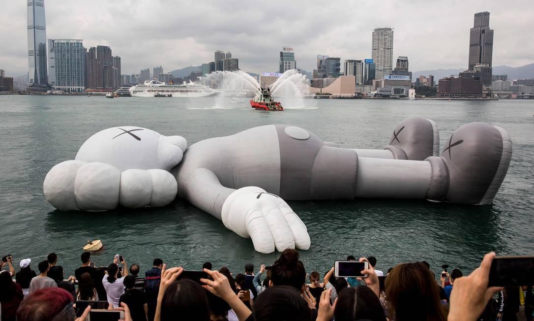 Uma escultura inflável do artista e designer americano Brian Donnelly, conhecido como Kaws, é exibida no Victoria Harbour durante a cerimônia de abertura de sua exposição em Hong Kong. Feito em colaboração com o estúdio criativo local AllRightsReserved (ARR), a escultura KAWS: HOLIDAY, de 37 metros de comprimento, será ancorada no Porto Victoria Foto: ISAAC LAWRENCE / AFP
