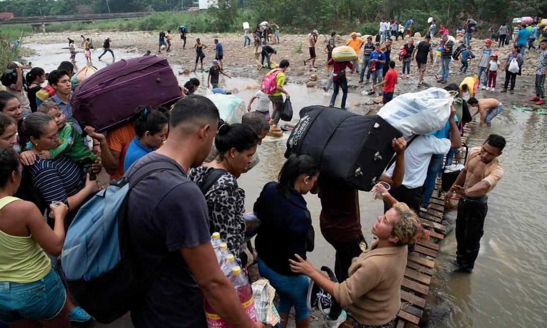 As pessoas atravessam de Cúucuta, na Colômbia, de volta a San Antonio del Táchira, na Venezuela, depois de comprar mercadorias para revender, por uma ponte improvisada em uma trilha ilegal na fronteira entre os dois países, perto da Ponte Internacional Simón Bolívar Foto: JUAN PABLO BAYONA / AFP