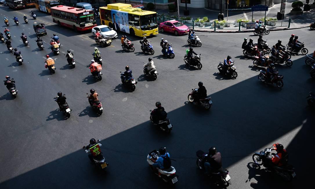 Motoristas se deslocam por um cruzamento em Bangkok, na Tailândia Foto: YE AUNG THU / AFP