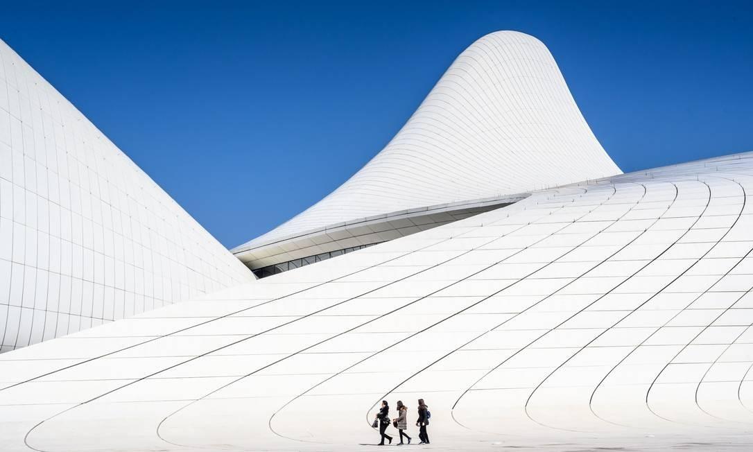Pessoas andam em frente ao Heydar Aliyev Center, em Baku, Azerbaijão. O edifício foi projetado pela arquiteta iraquiana-britânica Zaha Hadid e é considerado um dos marcos arquitetônicos mais reconhecidos em todo o mundo Foto: MLADEN ANTONOV / AFP