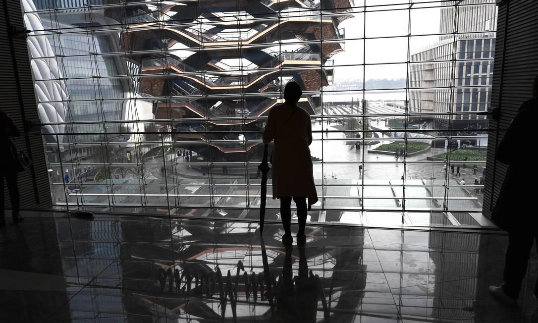 """Uma mulher observa o novo marco urbano de Nova York, temporariamente conhecido como o """"Navio"""" Foto: TIMOTHY A. CLARY / AFP"""