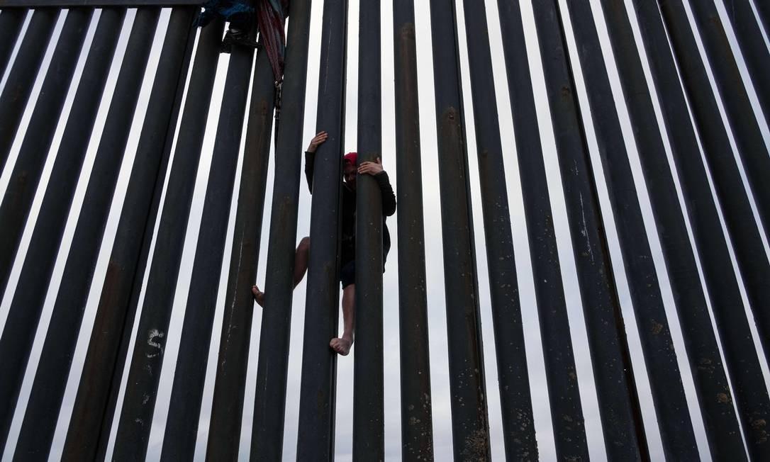 Um migrante da América Central cruza a cerca da fronteira EUA-México de Tijuana a San Diego, visto de Playas de Tijuana, no estado de Baixa Califórnia, México Foto: GUILLERMO ARIAS / AFP