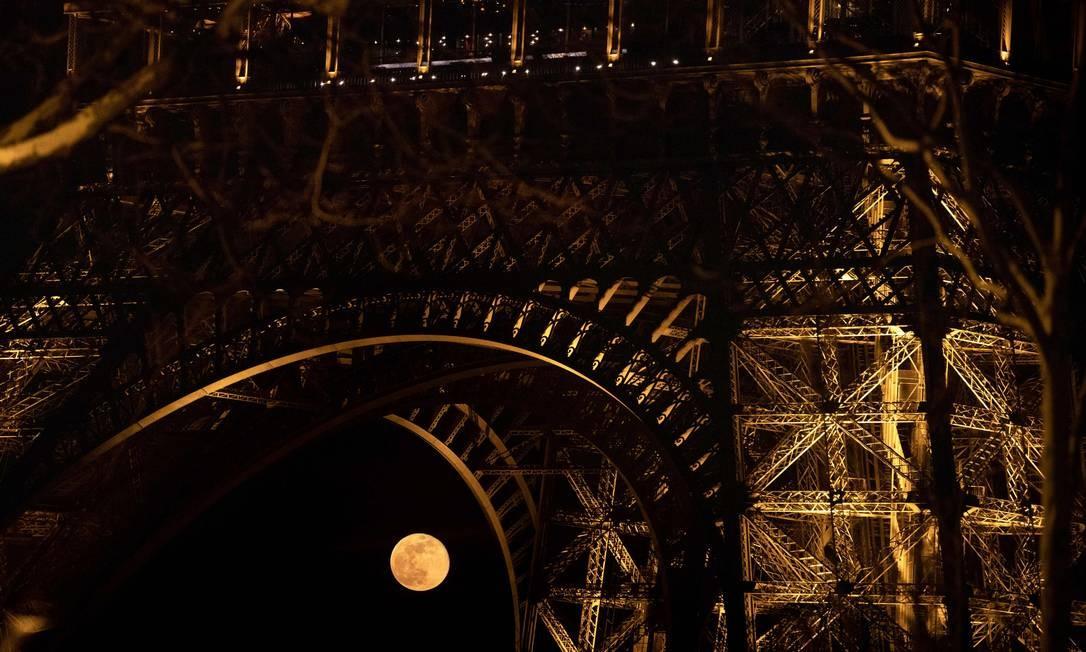 Foto tirada em 21 de março mostra a lua cheia atrás da Torre Eiffel, em Paris Foto: KENZO TRIBOUILLARD / AFP