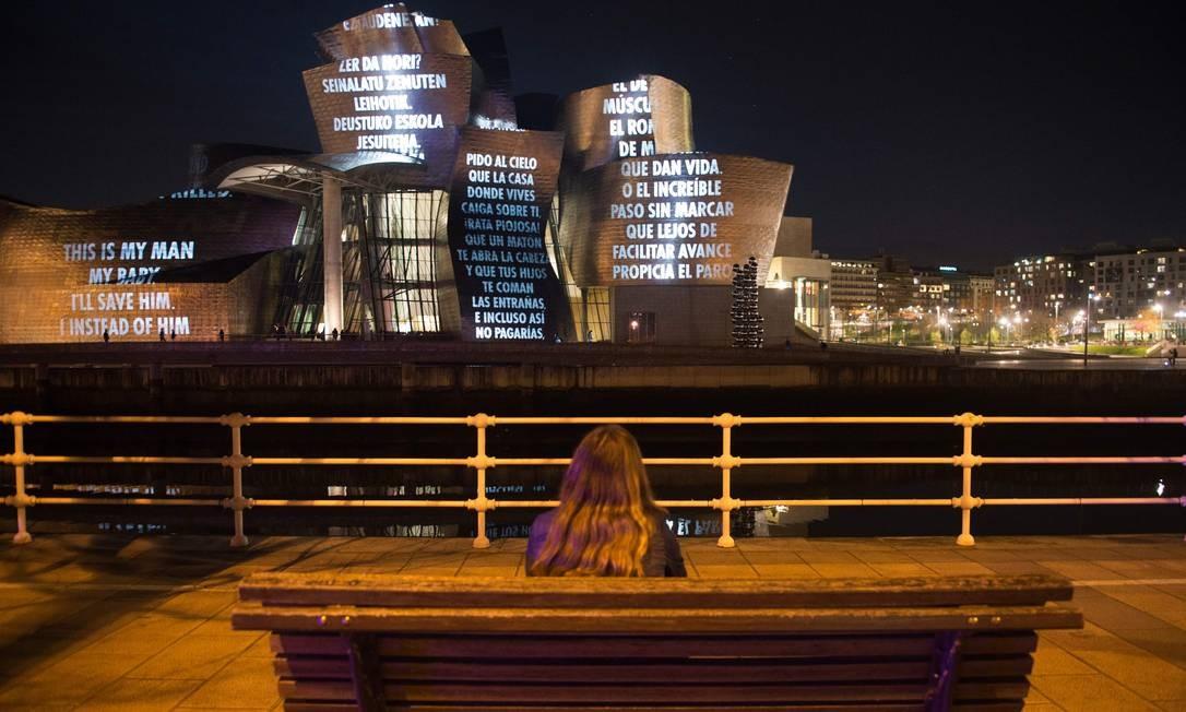 """Uma mulher assiste à projeção criada pelo artista americano Jenny Holzer, intitulada """"Para Bilbao"""", na fachada do Museu Guggenheim Bilbao, como parte da exposição """"Jenny Holzer: Coisa Indescritível"""", na cidade basca espanhola de Bilbao Foto: ANDER GILLENEA / AFP"""