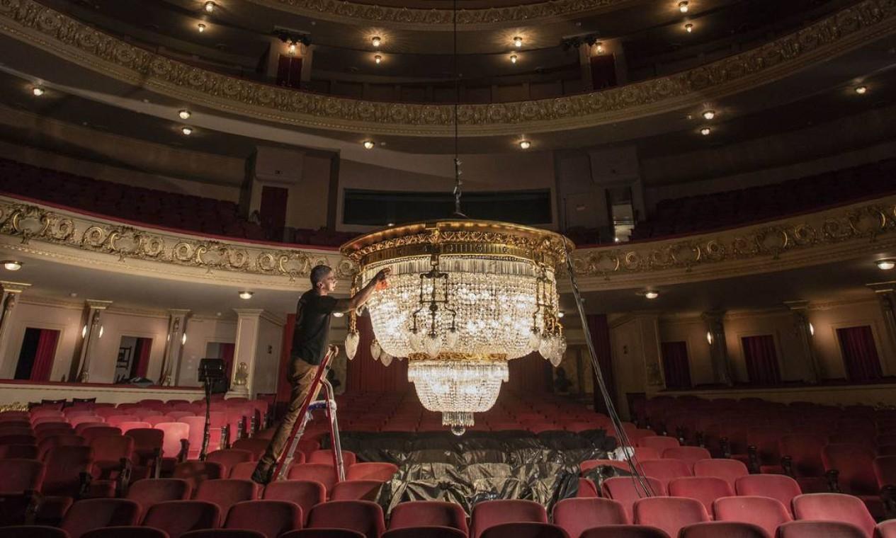 A manutenção do lustre da plateia é feita sob a supervisão do restaurador Alex Miranda Ribeiro, há décadas funcionário do teatro. Foto: Ana Branco / Agência O Globo