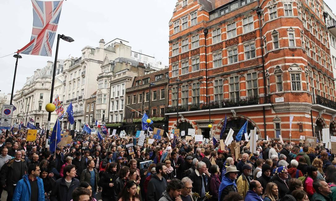 Pessoas carregam placas e levam bandeiras da União Europeia durante a passeata por um segundo referendo Foto: Isabel Infantes / AFP