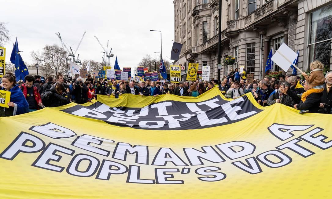 Pessoas exibem uma enorme faixa convocando uma nova votação Foto: Niklas Halle'n / AFP